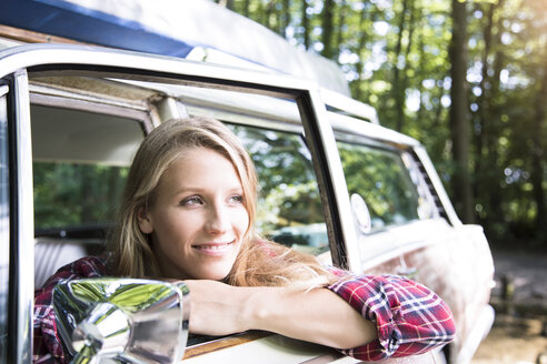 Smiling young woman in car in forest - FKF02800