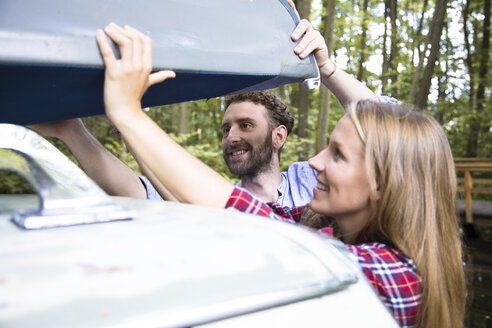 Smiling young couple taking canoe from car roof - FKF02803