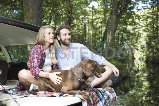 Smiling young couple with dog sitting in car at a brook in forest - FKF02806 - Florian Küttler/Westend61