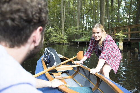 Happy young couple entering canoe in a forest brook - FKF02809