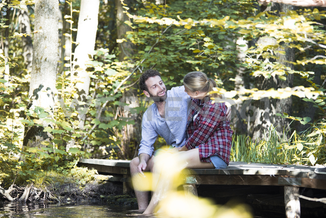 Young couple sitting on a bridge in forest with feet in water - FKF02812 - Florian Küttler/Westend61