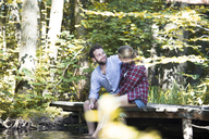 Young couple sitting on a bridge in forest with feet in water - FKF02812