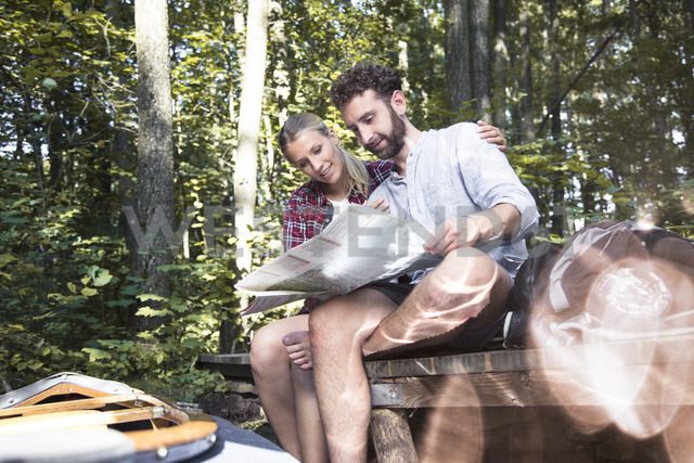 Young couple with map and canoe sitting on a jetty at a forest brook - FKF02815