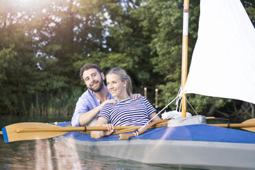 Happy young couple enjoying a trip in a canoe with sail - FKF02818