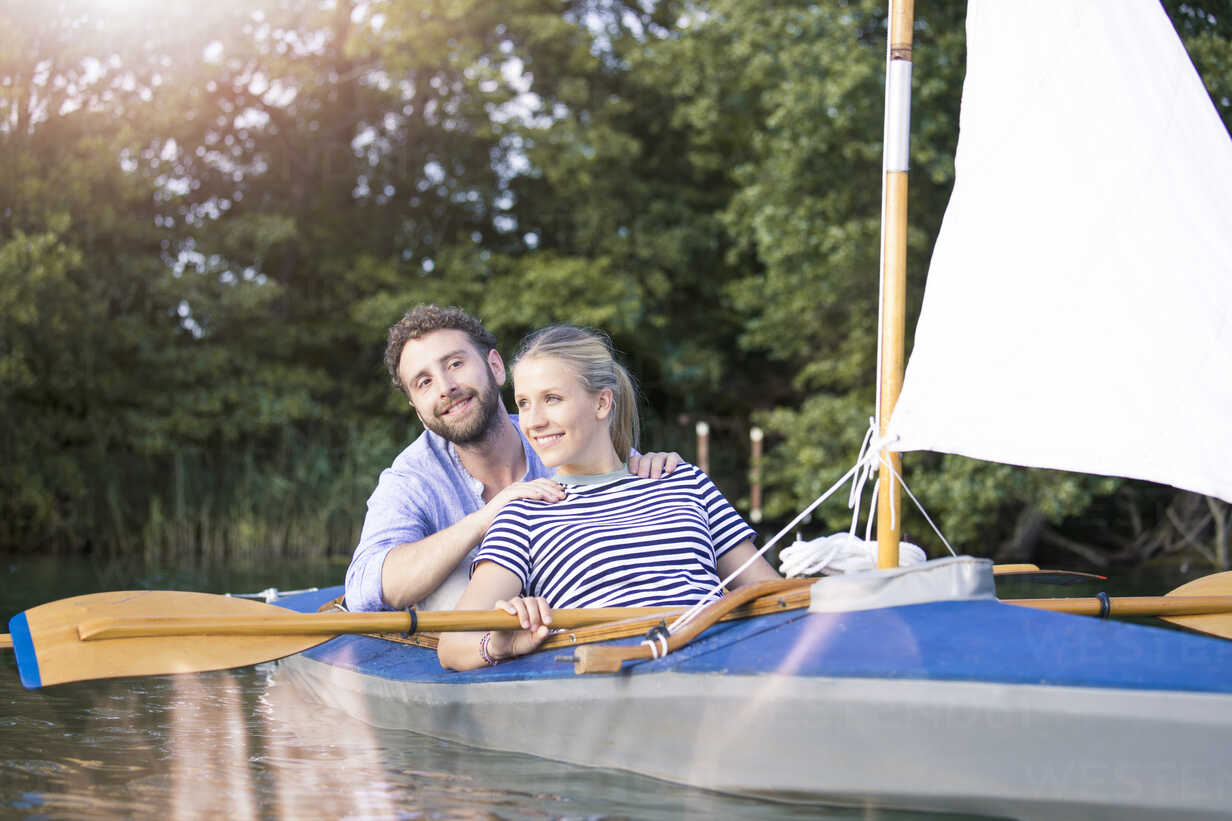 Happy young couple enjoying a trip in a canoe with sail - FKF02818 - Florian Küttler/Westend61