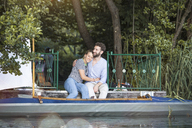 Happy young couple with canoe sitting on a jetty - FKF02821