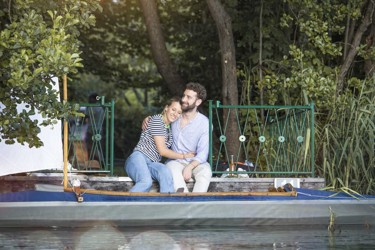 Happy young couple with canoe sitting on a jetty - FKF02821 - Florian Küttler/Westend61