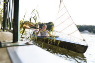 Young couple enjoying a trip in a canoe with sail on a lake - FKF02824