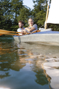 Young couple enjoying a trip in a canoe with sail on a lake - FKF02827