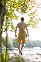 Young man with surfboard walking on a jetty at a lake - FKF02842