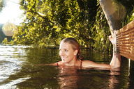 Happy young woman in a lake - FKF02848