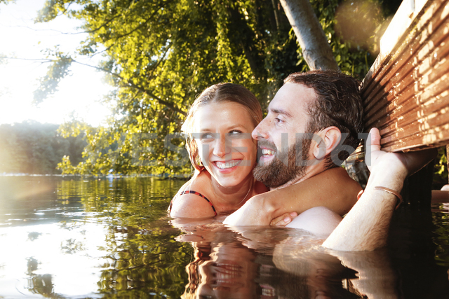 Happy young couple in a lake - FKF02851
