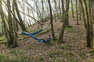 Germany, Rhineland-Palatinate, Vulkan Eifel, young man lying in hammock in forest - GUSF00280