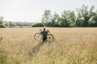 Young man carrying his bike, field - GUSF00283