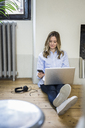 Woman sitting on the floor at home using cell phone and laptop - GIOF03602