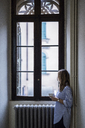 Woman with cup of coffee at home looking out of window - GIOF03608