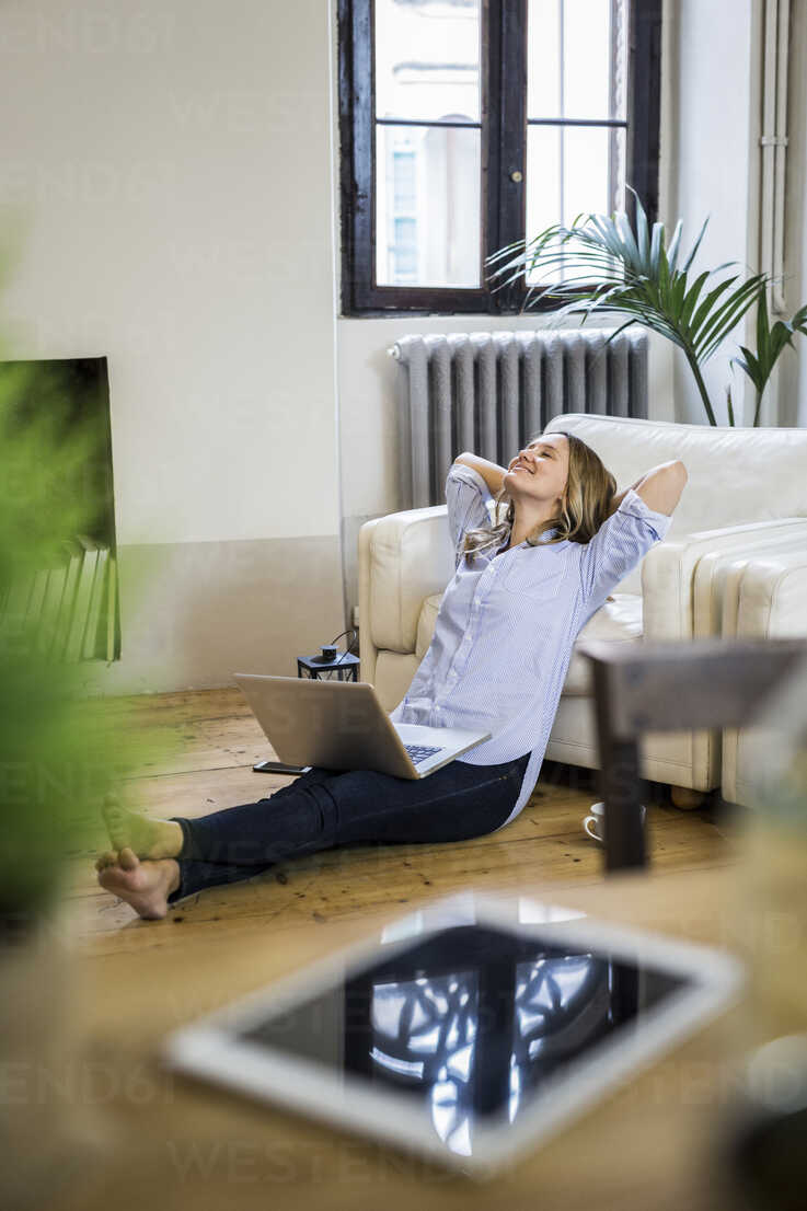 Smiling woman with laptop at home leaning back - GIOF03617 - Giorgio Fochesato/Westend61