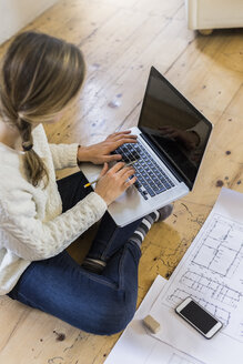 Woman sitting on the floor with blueprint using laptop - GIOF03623