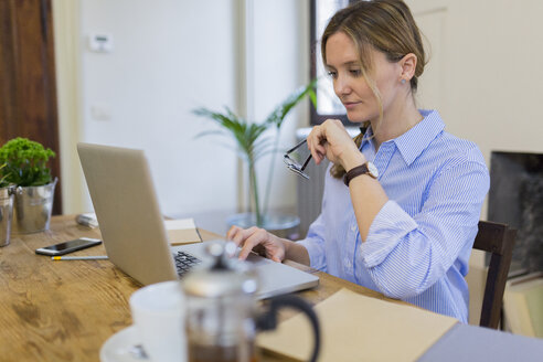 Woman using laptop on wooden desk at home - GIOF03632