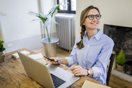 Smiling woman sitting at wooden desk at home looking sideways - GIOF03635