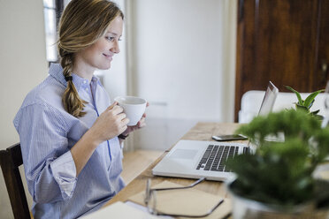 Smiling woman sitting at desk with cup of coffee and laptop - GIOF03647