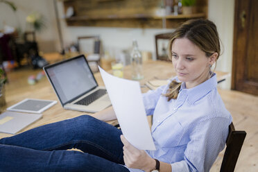 Woman sitting at desk at home with feet up reading document - GIOF03656