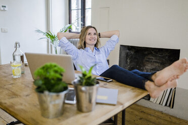 Smiling woman sitting at desk at home with feet up - GIOF03659