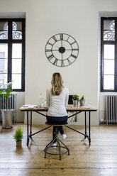 Rear view of woman sitting at desk at home under large wall clock - GIOF03662