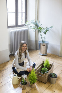 Portrait of smiling woman sitting on floor at home caring for plants - GIOF03677