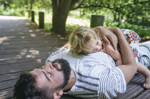 Little girl hugging her father lying on a wooden walkway in the countryside - DAPF00844