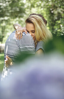 Romantic couple hugging behind an unfocused bouquet of flowers - DAPF00865