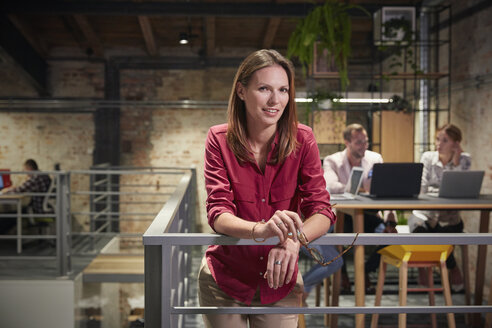 Businesswoman standing in office holding smartphone - WESTF23797