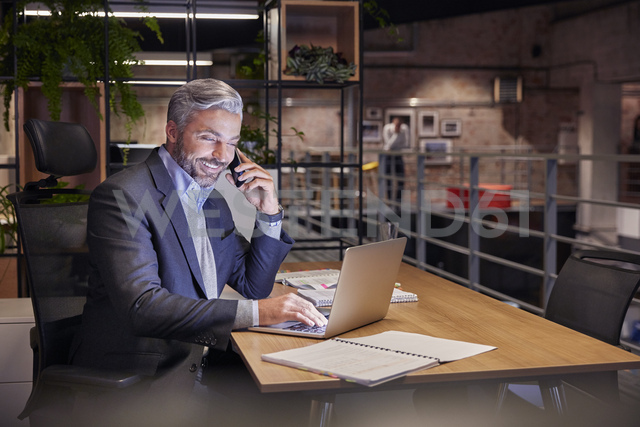 Mature businessman working in modern office, using laptop while talking on the phone - WESTF23800