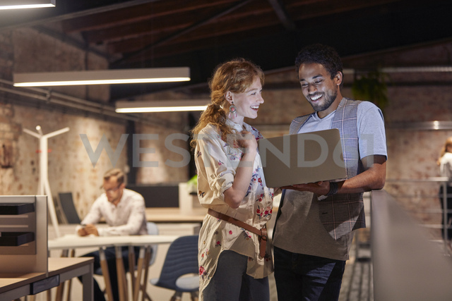 Man in office holding laptop, talking to colleague - WESTF23806