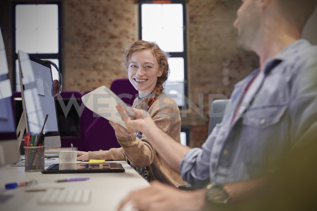 Young man helping colleague sitting at desk in office, smiling - WESTF23821