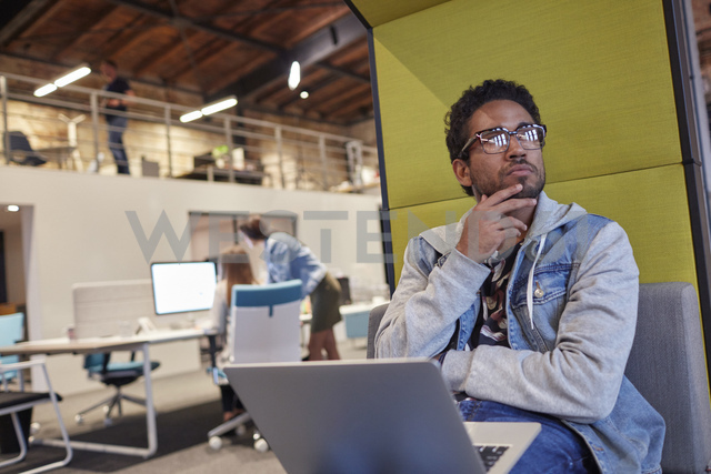 Young man working in creative start-up company, using laptop - WESTF23827