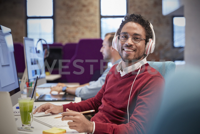 Young man sitting at desk in office, wearing headphones, smiling - WESTF23836
