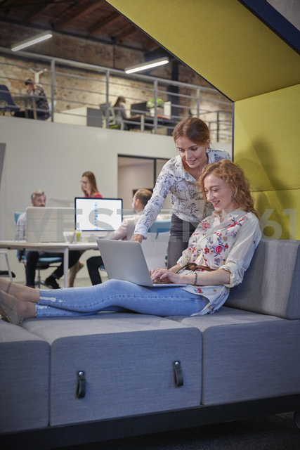 Young woman working in modern creative office, using laptop - WESTF23854