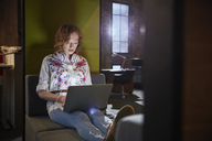 Young woman sitting on couch  working on laptop - WESTF23857