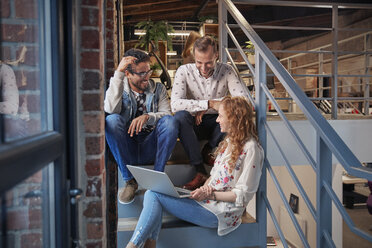 Young business people sitting on stairs in loft office using laptop - WESTF23860