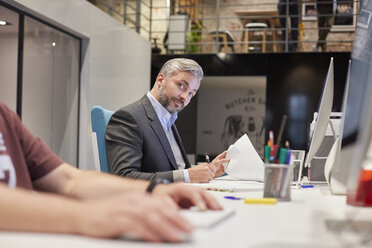 Businessman sitting at desk in office, looking curious - WESTF23872