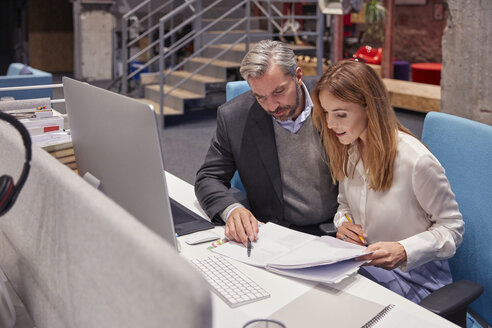 Businessman and woman working together in modern office - WESTF23875