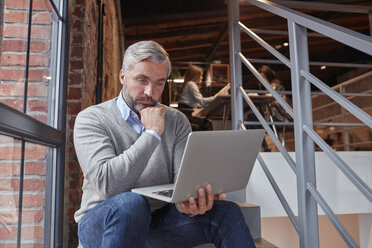 Businessman sitting on stairs of modern office, using laptop - WESTF23887