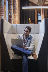 Young man working in creative start-up company, using laptop - WESTF23890
