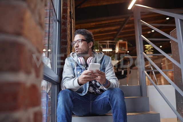 Young man working in creative start-up company, using smartphone - WESTF23893