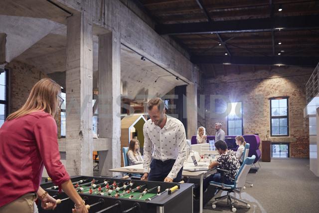 Business people in office taking a break, playing foosball - WESTF23902