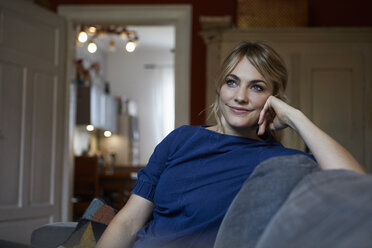Portrait of smiling woman relaxing on couch at home - RBF06169