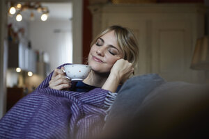 Portrait of smiling woman with cup of tea relaxing on couch at home - RBF06172