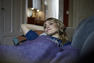 Smiling woman relaxing on couch at home - RBF06175