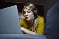 Portrait of woman lying on the couch using headphones and laptop - RBF06178